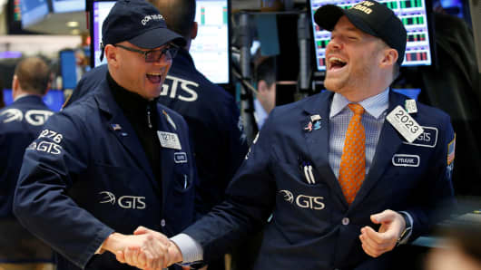Traders celebrate on the main trading floor of the New York Stock Exchange as the Dow Jones industrial average passes the 20,000 mark shortly after the opening of the trading session in New York, January 25, 2017.