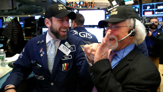 Traders celebrate on the main trading floor of the New York Stock Exchange (NYSE) as the Dow Jones Industrial Average passes the 20,000 mark shortly after the opening of the trading session in New York, U.S., January 25, 2017.