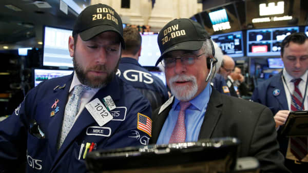 Traders work on the main trading floor of the New York Stock Exchange as the Dow Jones industrial average passes the 20,000 mark shortly after the opening of the trading session on Jan. 25, 2017.