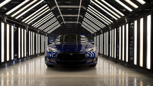 A Tesla Model S automobile stands in a light tunnel.