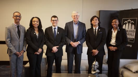 Charles Koch flanked by Thurgood Marshall College Fund students.