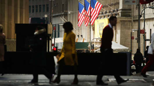 Pedestrians walk outside of the New York Stock Exchange.
