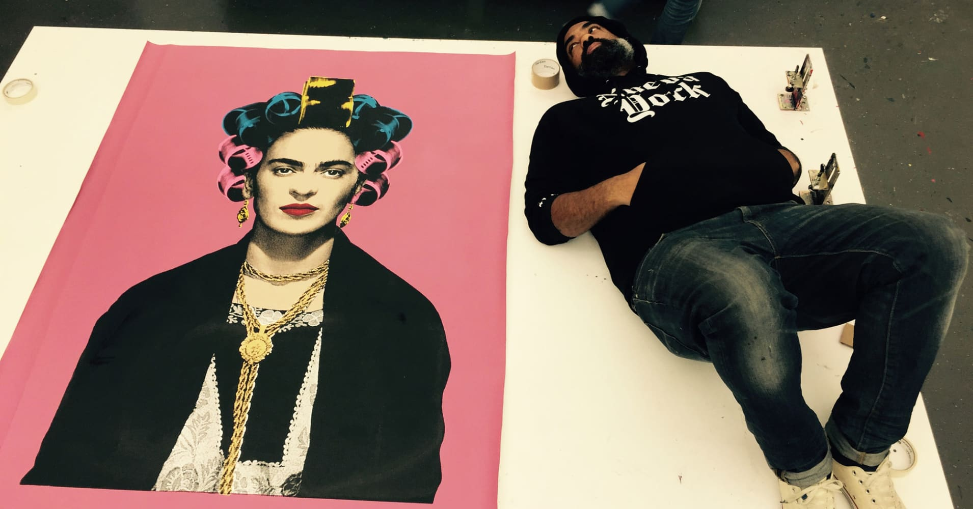 M. Tony Peralta, founder of the Peralta Project, lays down next to his canvas of Frida Kahlo.