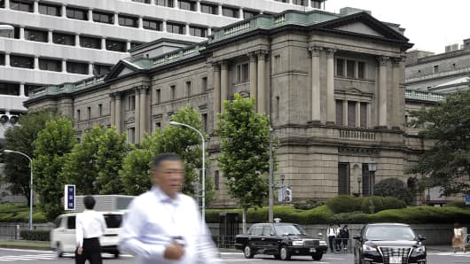 Pedestrians cross a road in front of the Bank of Japan (BOJ) headquarters in Tokyo, Japan, on Wednesday, Sept. 21, 2016.