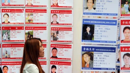 A woman looks at pictures of people at a dating agency at the Shanghai Marriage Expo.