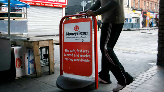 A shop worker places a sign for 'MoneyGram' outside his store on Moore Street in Dublin, Ireland.