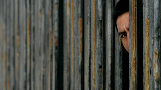 A Mexican National peers through the U.S. Mexico border wall in San Ysidro, California.