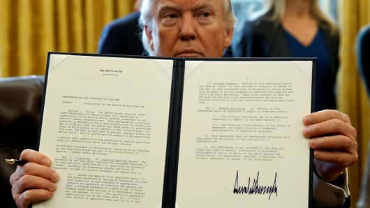 President Donald Trump holds up a signed executive order to advance construction of the Dakota Access pipeline, at the White House in Washington on January 24, 2017.
