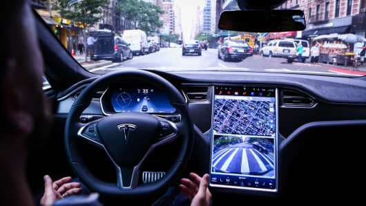 A driver rides hands-free in a Tesla Motors Inc. Model S vehicle equipped with Autopilot hardware and software in New York.