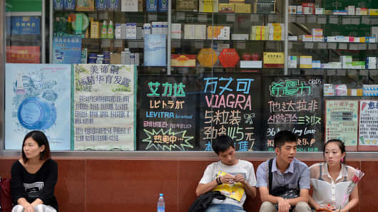 Chinese shoppers wait outside pharmacy selling medicine in Beijing.