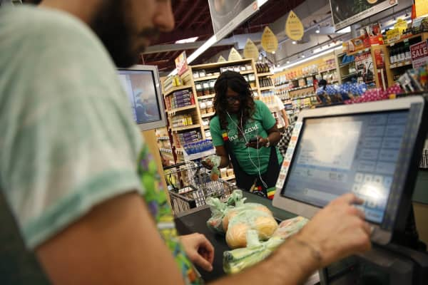 Whole Foods cashier Jason Ellsworth rings up groceries.