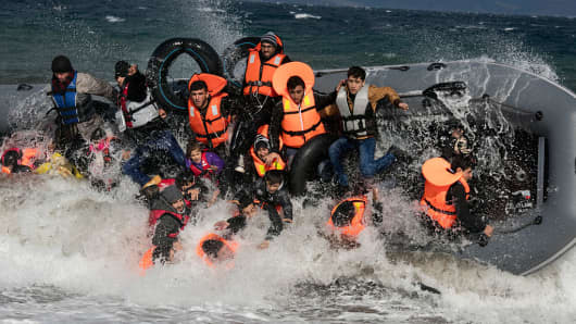 Refugees arriving to the island of Lesbos fall out of a boat as it capsizes on landing in rough seas coming from Turkey on October 31, 2015 in Lesbos, Greece.