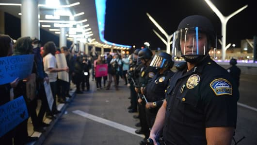 Police wearing riot gears and demonstratos are seen inside Los Angeles International Airport (LAX) in Los Angeles, California, United States on January 29,2017.