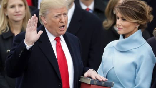 President Donald Trump takes the oath of office as his wife Melania Trump holds the bible on the West Front of the U.S. Capitol on January 20, 2017.