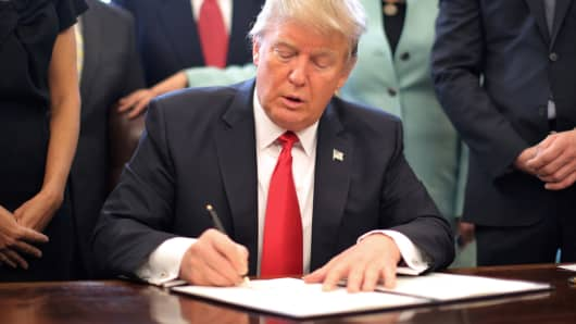 Surrounded by small-business leaders at the White House, President Donald Trump signs an executive order cutting regulations on Jan. 30, 2017.
