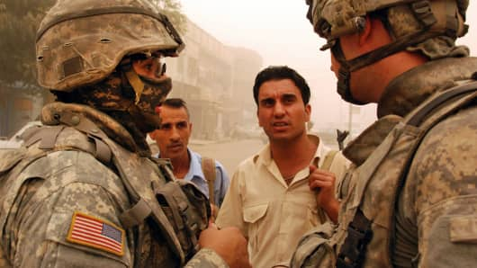 A masked interpreter, left, patrols the streets of Baghdad with a US Army unit.