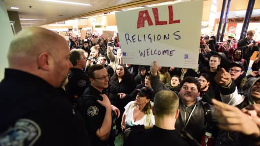 Protesters hold banners during a demonstration against President Trump's immigration ban at Portland International Airport in Portland, Oregon on January 29, 2017.