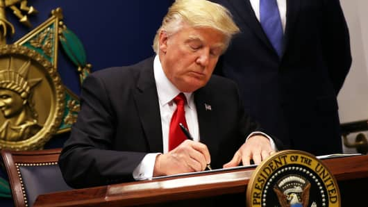 President Donald Trump signs an executive order to impose tighter vetting of travelers entering the United States, at the Pentagon in Washington, January 27, 2017.