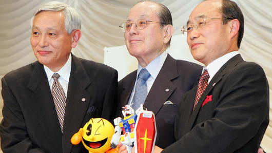 Masaya Nakamura (C) shakes hands with Takeo Takasu (R) and Kyushiro Takagi (L) during a press conference.