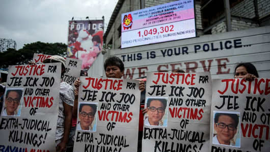 Activists hold a protest in front of Camp Crame, the headquarters of the Philippine National Police (PNP), hold placards showing the picture of the late South Korean businessman Jee Ick-Joo, who was murdered allegedly by suspected policemen in Manila on January 27, 2017.