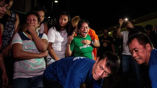 This picture taken on January 5, 2017, shows relatives crying as coroners carry away the body of an alleged drug dealer killed during a drug buy bust operation in Manila.