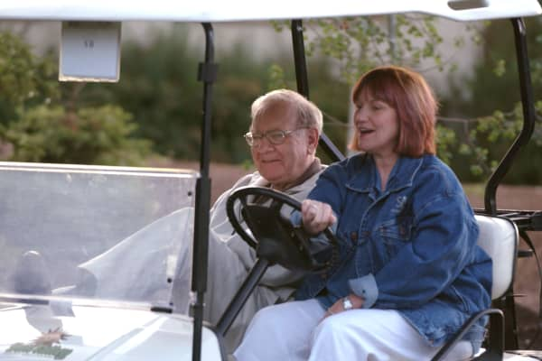 Warren Buffett, left, rides in a golf cart on his way into the Inn for sessions of the Allen & Co. conference in Sun Valley, Idaho.