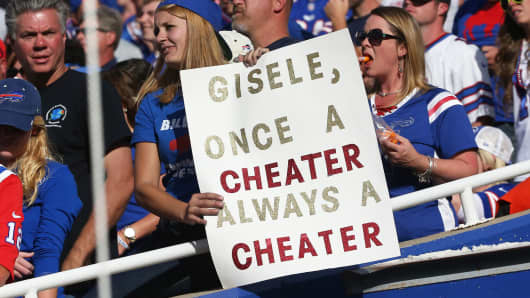 A fan of the Buffalo Bills holds up a sign jeering Tom Brady of the New England Patriots during NFL game action at Ralph Wilson Stadium in Orchard Park, New York.