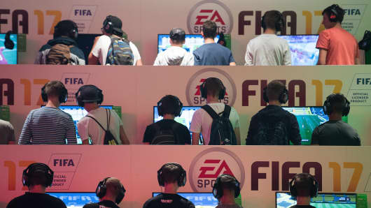 Visitors playing the game FIFA 17 at the EA Sports stall at the Gamescom gaming convention on August 18, 2016 in Cologne, Germany.