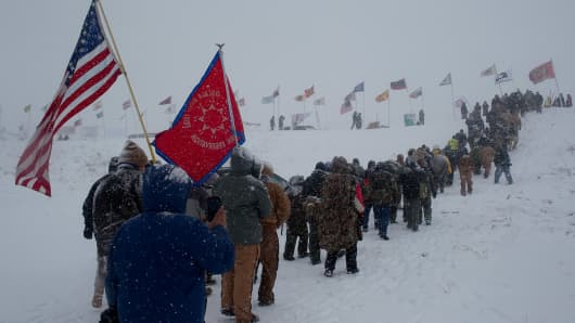 Hundreds of United States military veterans vow to defend the Standing Rock protest camp and march through a winter blizzard to the scene of recent clashes with state police and the national guard just outside of the Lakota Sioux reservation of Standing Rock, North Dakota, December 5, 2016.