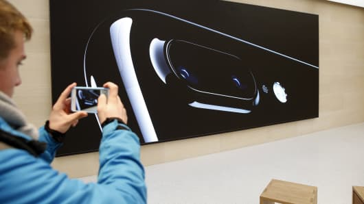 A customer takes a picture with an iPhone 7 inside the new Apple store Saint- Germain during the first opening day on December 03, 2016 in Paris, France.