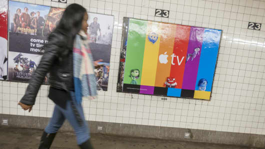A commuter walks past a poster advertising the AppleTV streaming video product, next to a Hulu ad, in the subway in New York.