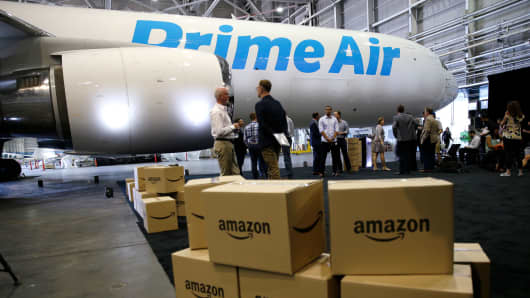 "Amazon.com boxes are shown stacked near a Boeing 767 Amazon ""Prime Air"" cargo plane on display in a Boeing hangar in Seattle."