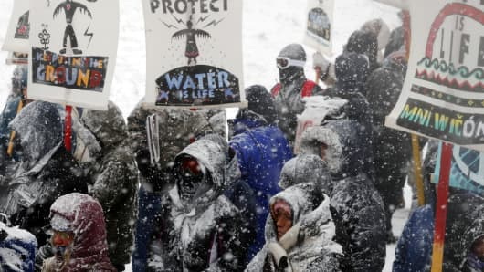 "Veterans march with activists near Backwater Bridge just outside of the Oceti Sakowin camp during a snow fall as ""water protectors"" continue to demonstrate against plans to pass the Dakota Access pipeline adjacent to the Standing Rock Indian Reservation, near Cannon Ball, North Dakota."