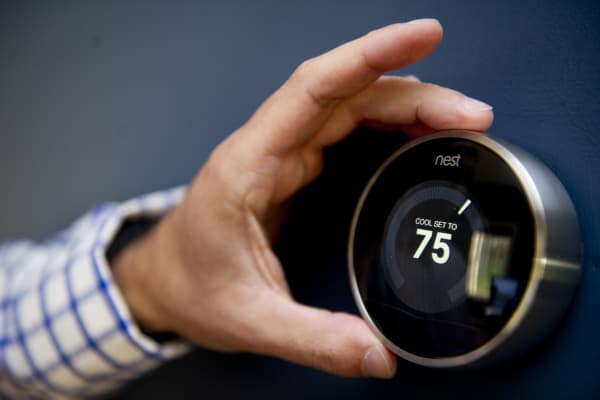 Nick DeLena adjusts his thermostat from Nest Labs in his home.