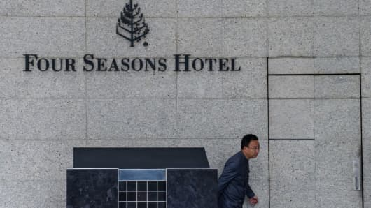 A member of staff walks outside the Four Seasons Hotel in Hong Kong on February 1, 2017. Financier Xiao Jianhua, founder of Beijing-based Tomorrow Group, was staying at the hotel before he disappeared, according to overseas Chinese-language media.