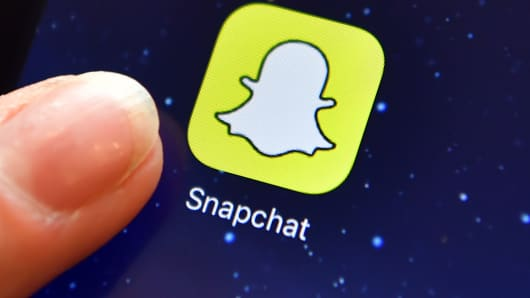 A finger is posed next to the Snapchat app logo on an iPad.
