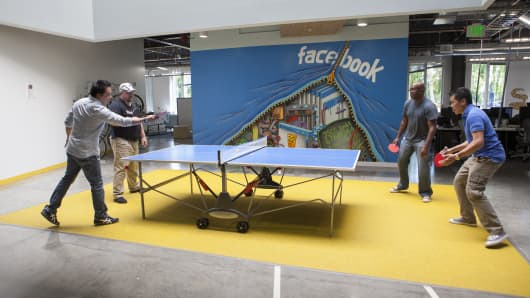 Facebook employees relax with a game of ping-pong on campus.