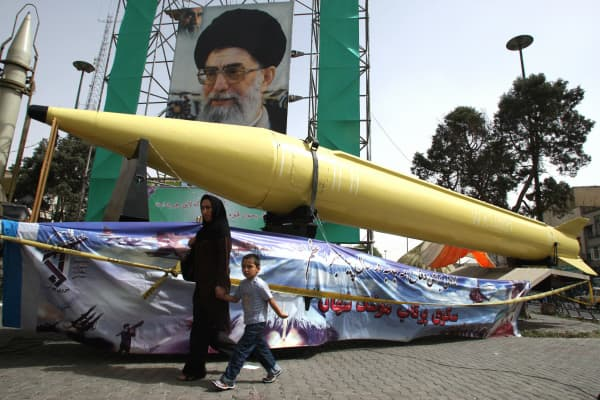 An Iranian woman and her son walk past Shahab-2 (L) and Shahab-3 missiles on display in front of a large portrait of Iran's Supreme Leader Ayatollah Ali Khamenei in a square in south Tehran.