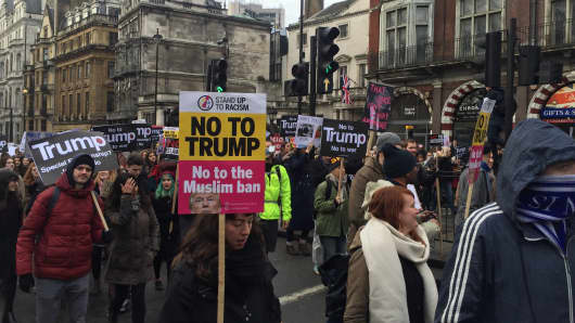 "Protesters held black banners with blood stains bearing slogans such as ""No to Trump. No to War."""