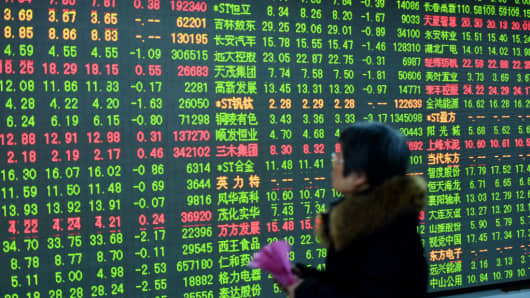 An investor watches the electronic board at a stock exchange hall on February 3, 2017 in Hangzhou, Zhejiang Province of China.