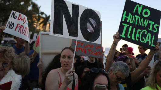 People protest against President Donald Trump as they gather to walk toward Mar-a-Lago Resort where he is staying for the weekend on February 4, 2017 in Palm Beach, Florida.