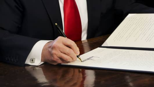 U.S. President Donald Trump signs an Executive Order related to the review of the Dodd-Frank Act in the Oval Office of the White House, in Washington, D.C., U.S., on Friday, Feb. 3, 2017.