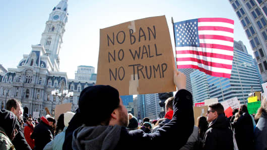 A protester holds a sign and the American Flag as demonstrators gather to protest against President Donald Trump's executive order banning refugees and immigrants from seven primarily Muslim countries during a rally in Philadelphia, February 4, 2017.