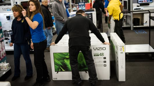 An employee arranges a display of Vizio Inc. high-definition televisions at a Best Buy Inc. store in Paramus, New Jersey.