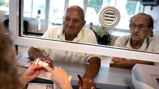 A man picks up his prescription medication at the CAC-Florida medical center pharmacy.