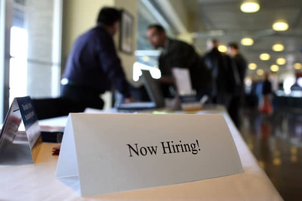 A 'now hiring' sign is posted on a table during the Recruit Military Career Fair.
