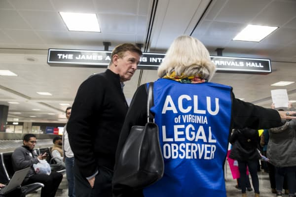 Rep. Don Beyer, D-Va., speaks with an ACLU legal observer during the protest at Dulles International Airport in Virginia on Sunday, Jan. 29, 2017.
