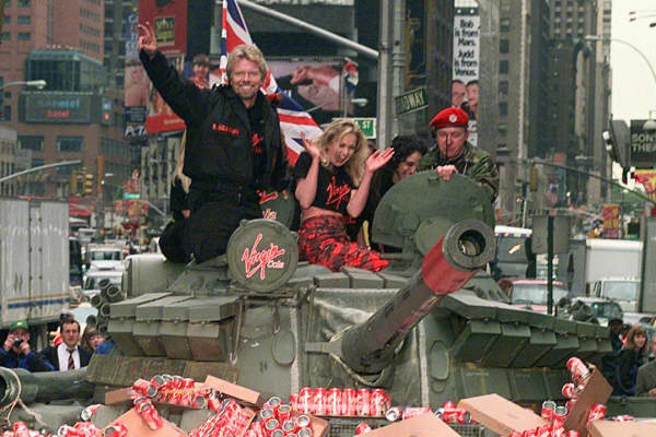 Virgin Chairman Richard Branson, at left on top of tank, flashes a V-for-victory sign as his vehicle crashes through a wall of Virgin Cola cans in New York's Times Square, Tuesday May 12, 1998.