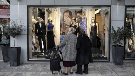 Pedestrians look at a clothing store window display in Aristotelous square in Thessaloniki, Greece, on Thursday, Dec. 1, 2016.