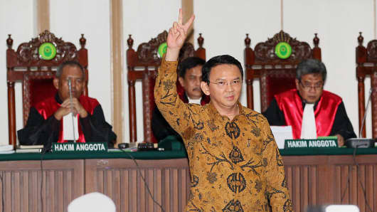 Jakarta's Christian governor Basuki Tjahaja Purnama (foreground), better known by his nickname Ahok, flashes a victory sign as he appears in court for his ongoing trial in Jakarta on Jan. 3, 2017.
